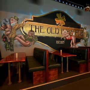 The Old Irish Pubs väggmålning i Vasa med kåt leprechaun och lättklädda brudar.