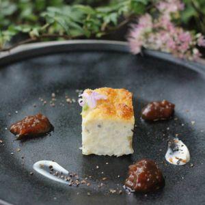 Liten bit pannkaka på svart tallrik med sake-aprikoskompott.