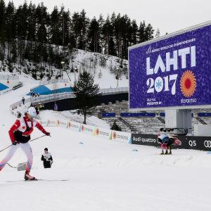 En skidåkare i Lahtis, framför en skylt där det står Lahti 2017.