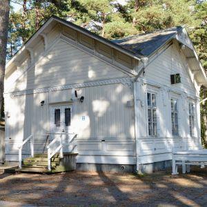 Vit gammal trähusbyggnad i ett parkområde.