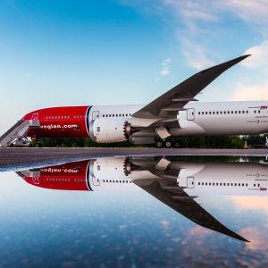 Ett Norwegian-plan speglas i vattnet.