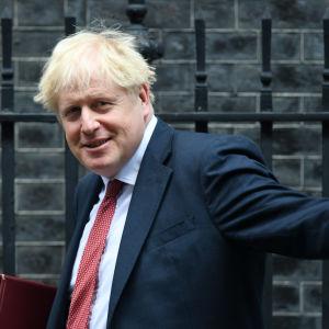 Boris Johnson heilauttaa kättään.