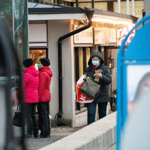 Människor på gata tittar in genom skyltfönster, i förgrunden blå och svarta reklamtavlors kanter.
