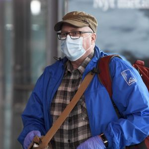 En man iförd ansiktsskydd på Helsingfors-Vanda flygplats.