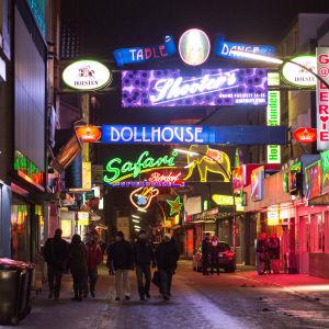 Människor går på en gata omringad av sexbutiker.