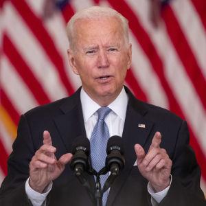 Joe Biden pratar vid ett talarpodium. I bakgrunden syns USA:s rödvit-randiga flagga.