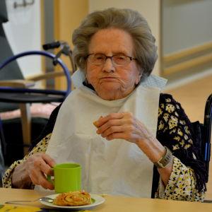 En äldre gråhårig dam äter bulla.