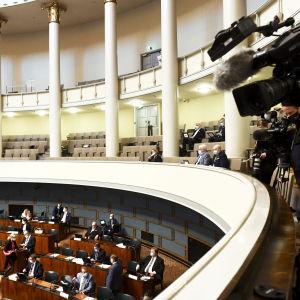 Kameror på riksdagens pressläktare, riktade mot Sannfinländarna i plenisalen.