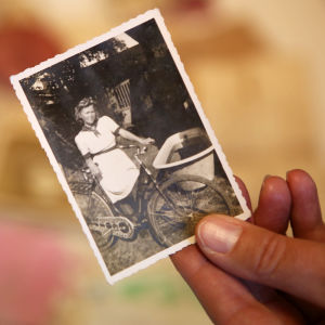En person håller i ett gammalt svartvitt fotografi mellan tummen och pekfingret. På bilden står en ung flicka i vit klänning med en cykel.