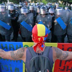 Demonstrant håller upp plakat framför en rad rumänska poliser i Bukarest.