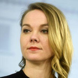 Katri Kulmuni en ung kvinna med blont axellångt hår och gröna ögon tittar förbi kameran. Bakgrunden är suddig och grå.