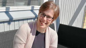 En kvinna med kort rödblont hår och glasögon sitter på en svart polyrottingbänk vid en vit-grå husvägg. Solen skiner och kisar lite med ögonen. Hon ler.