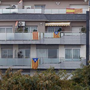 Både katalanska och spanska flaggor pryder balkonerna vid ett höghus i Barcelona.