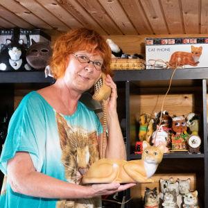 En kvinna håller en telefon formad som en katt i handen.
