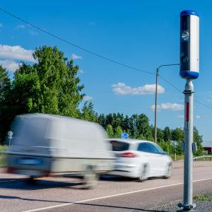 En personbil med släpkärra bakom passerar en kamera på en väg.