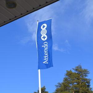 Attendos flagga vajar utanför pyttis hälsovårdscentral.