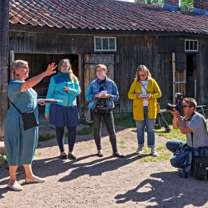 Ihmisryhmä Turussa Luostarimäen museoalueen puutalojen keskellä.