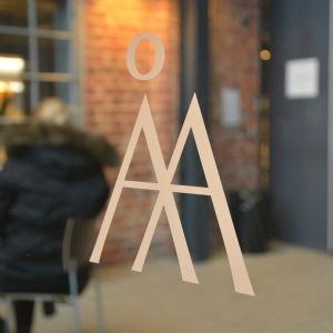 Åbo Akademis textlogo, ett Å och ett A klistrat på en glasdörr, insidan av huset med röd tegelvägg i bakgrunden.