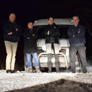 Fyra personer står framför en taxi med armarna i kors.