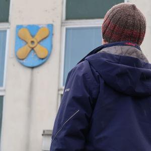 En man står och ser mot Kimitoöns vapen som hänger på en vägg.