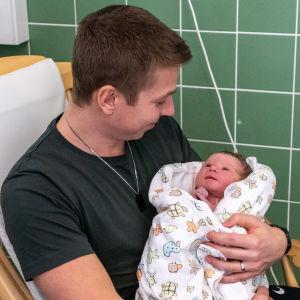 Lucas Lönnqvist sitter i gungstolen och har bebisen i famnen. Bebisen tittar på pappan som ler.