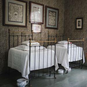 Kaksi vanhanaikaista sänkyä, seinällä tauluja, takaseinällä ikkuna ulos
