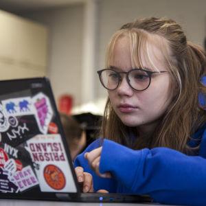 Trine Juutilainen ser på datorn.