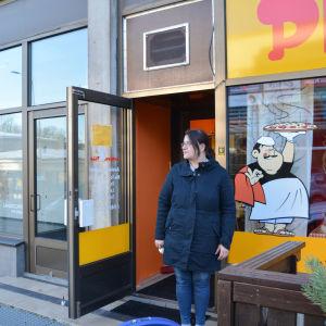 kvinna står i dörren till en pizzeria