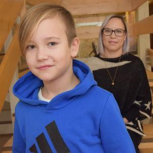 En tioårig pojke och en kvinna (hans mamma) sitter på olika trappsteg i en trappa inomhus.