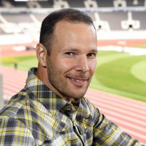 Tero Pitkämäki sitter på läktaren på Olympiastadion och ler mot kameran.