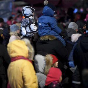 En folksamling på Medborgartorget i Helsingfors under nyårsafton 2019. Två barn sitter på två vuxnas axlar.