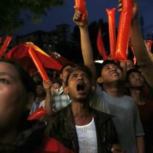 NLD-anhängare utanför partiets huvudkontor gläder sig över de första resultaten i Burmas parlamentsval.