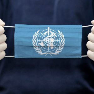 En person i vita skyddshandlas håller i ett munskydd med WHO:s logo.