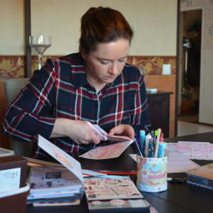 Tanja sitter vid bordet och klipper. På bordet finns också många pennor, klistermärken och kalendrar.