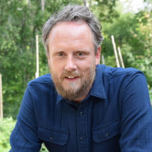 Porträtt på Strömsös kock Anders Samuelsson med skog i bakgrunden