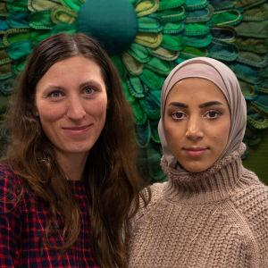 Två kvinnor som ler. Den ena har rutig klänning och den andra har en beige hijab och beige stickad tröja.