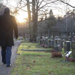 mies kävelee hautausmaalla