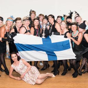 En grupp kvinnor i svarta klänningar står och håller i en pokal och en finsk flagga.