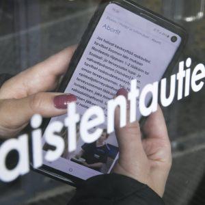 En person håller i en mobiltelefon med en finspråkig text om abort.