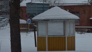 Ett litet, runt, gulmålat lusthus på Karis järnvägsområde. Syns inga tåg, men i bakgrunden ses en röd tegelbyggnad. Vinter och snö.