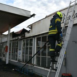 En bensinstation där taket brunnit. En brandman klättrar upp för en stege med vattenslang.
