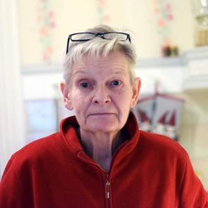 En äldre kvinna med röd fleecetröja och glasögon uppskuffade uppe på huvudet. Hon är i sitt kök.