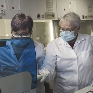 Tre kvinnor undersöker coronavirusprover i laboratoriemiljö.