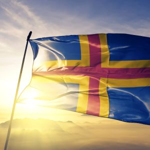 Ahvenanmaan lippu liehuu auringon noustessa.