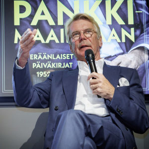 Björn Wahlroos lavalla puhumassa mikrofoniin. Taustana kuva hänen kirjansa kannesta.