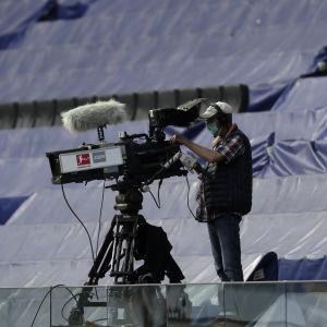 Kameramannen som filmar matchen mellan Eintracht Frankfurt och Borussia Mönchengladbach bär andningsskydd.