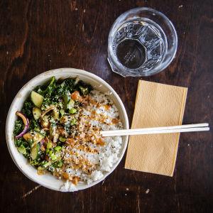 Poke bowl med lax och ris i en hämtmatsskål på ett bord.
