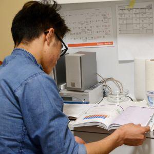 En ung man läser läxor vid ett skrivbord.
