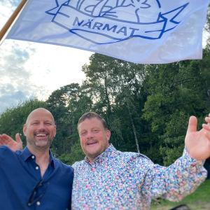 Matias och Micke står vi havet och skrattar in i kameran med Närmatsflaggan i handen.