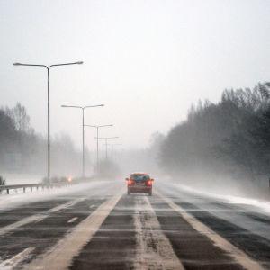 En bil kör på en motorväg, snön yr.